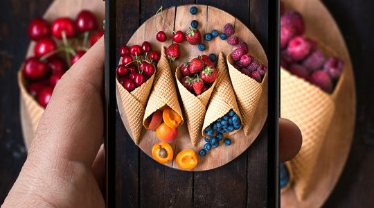 Man photographing fruits in ice cream cone with his cellphone camera,selective focus